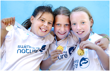 Three young girls holding medals wearing Swimming Nature t-shirts