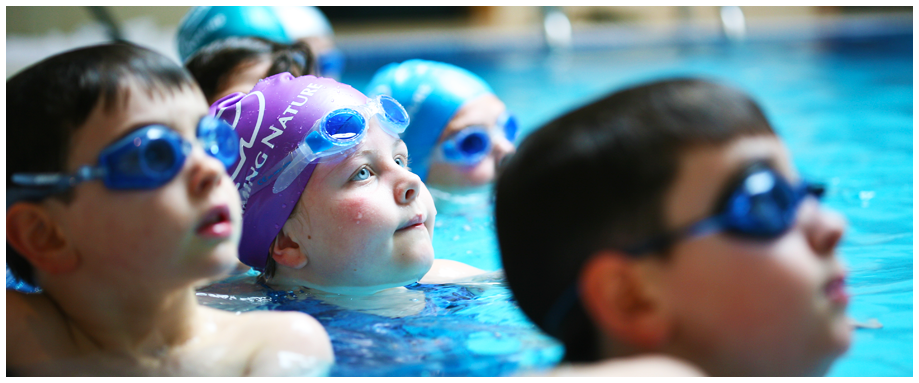 Young school children wearing goggles having a swimming lesson in a pool