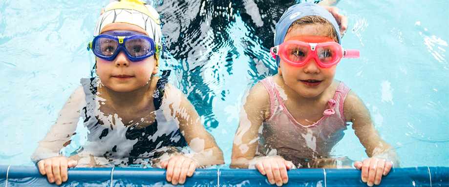 Young boy swimming frontcrawl with goggles and waterproof hat on