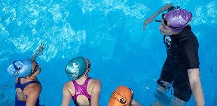Three children being taught by their female swimming instructor in a pool
