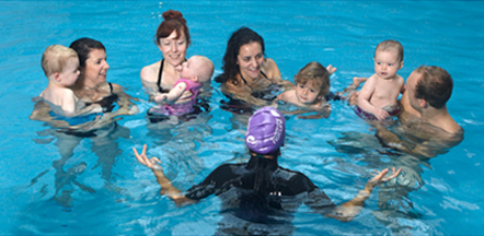 Group of women and men taking their babies for a swimming lesson