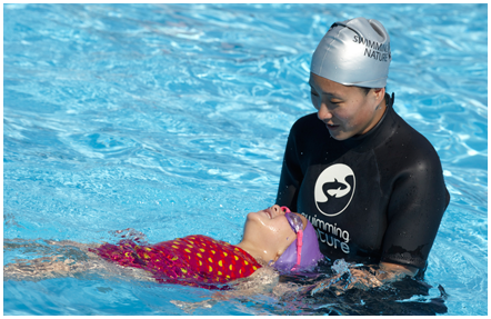 Female swimming instructor using a hands-on approach to train a young girl