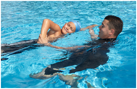 Male swimming instructor training a young student in-water